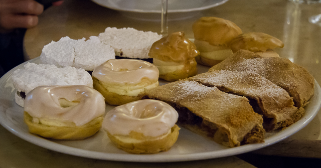 "Czech sweets: ""vetrnik"" (round windmill chaux pastry with caramel and cream filling and caramel glaze), ""venecek"" (chaux pastry with vanilla cream and a sugar glaze), apple strudel and ""laskonka"" (coconut merengue and chocolate cream)."